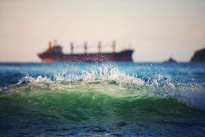 Sailing cargo ship and waves at sunrise. Transportation. Logistics. Shipping